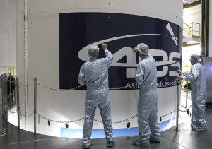 During earlier activity at the Spaceport, the ABS logo is placed on Ariane 5's payload fairing by launch team members working inside the Final Assembly Building.