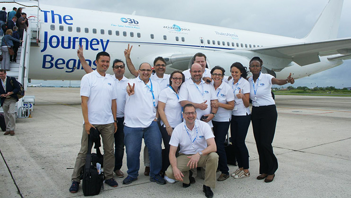 "O3b Networks team members show the company spirit in front of a chartered Boeing 767 that brought executives and guests from Paris to French Guiana for today's VS05 Soyuz mission. This aircraft carried the company's slogan for today's mission: ""The Journey Begins,"" along with the logos of O3b Networks, Arianespace and Thales Alenia Space."